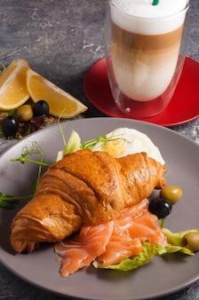 Вкусный круассан с копченым лососем и латте concept breakfast