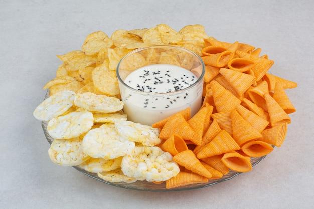 白い背景の上のソースとおいしいcrucnhyポテトチップス。高品質の写真