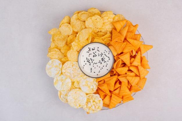 白い背景にヨーグルトとおいしいcrucnhyポテトチップス。高品質の写真