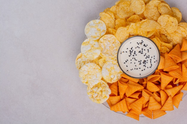 Tasty crucnhy potato chips with yogurt on white background. high quality photo