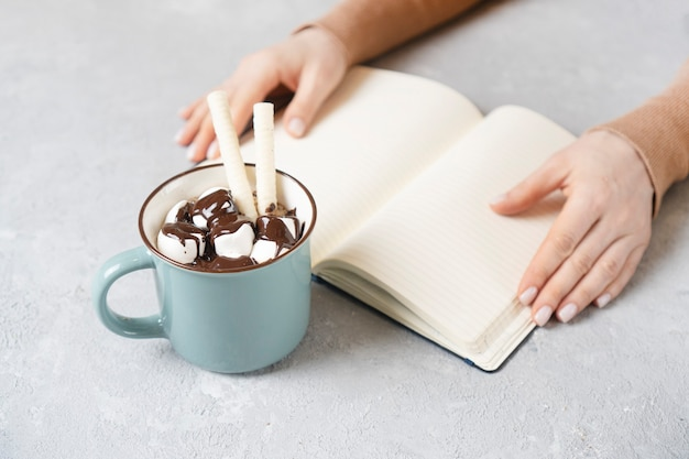 Tasty cup of coffee or cocoa. female hands with notebook on a backdrop.