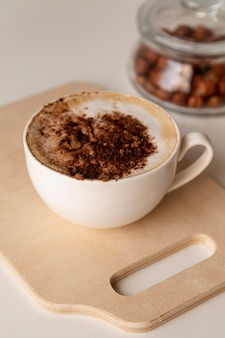 Tasty cup of coffee on wooden board