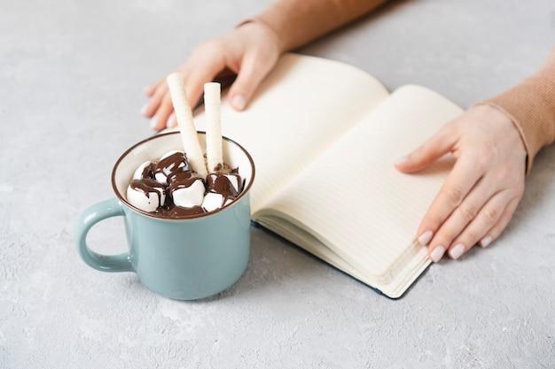 おいしいコーヒーまたはココア。背景にノートブックと女性の手。