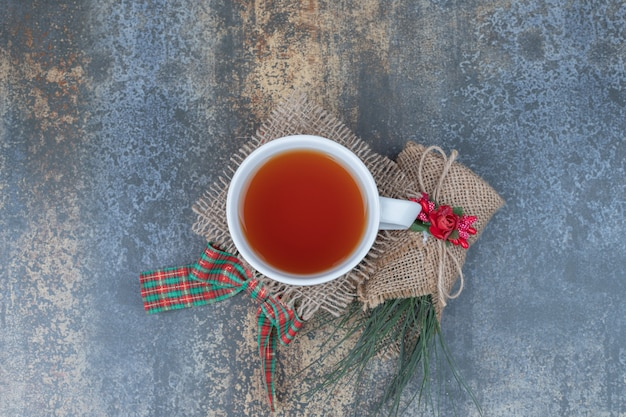 Gustosa tazza di tè con bellissimo fiocco su tela.