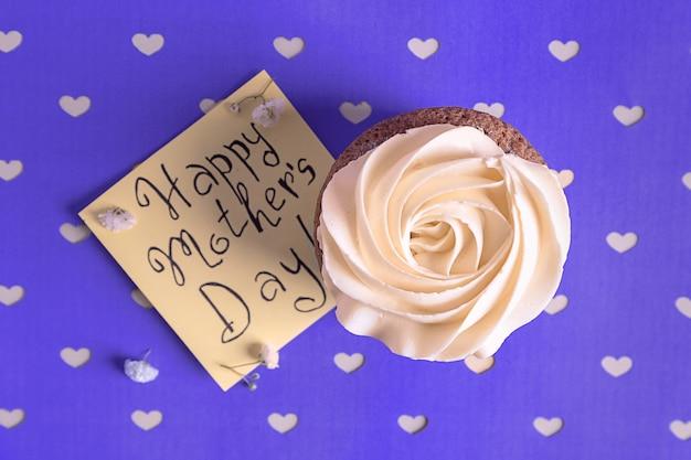 Вкусный кекс и открытка со словами с днем матери на цветном фоне