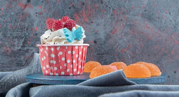 블루 보드에 크림과 사탕으로 장식 된 맛있는 컵 케이크