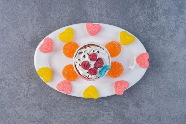 白いプレートにクリームとラズベリーで飾られたおいしいカップケーキ。