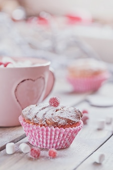 Tasty cupcake with berries and cup of coffee