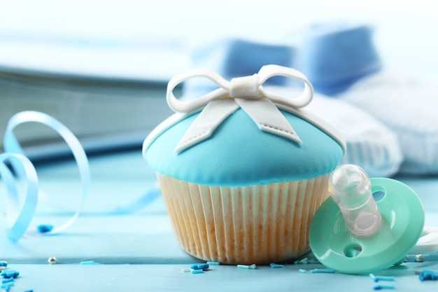 色の木製テーブルに弓と赤ちゃんの靴とおいしいカップケーキ