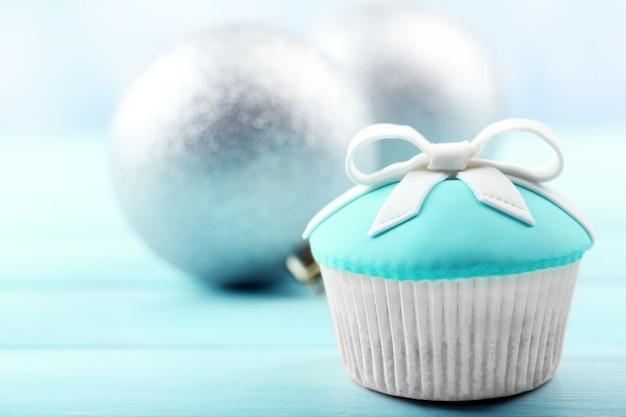 色の木製の背景に弓とクリスマスのおもちゃとおいしいカップケーキ