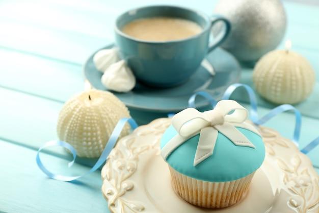 色の木製の背景に弓、コーヒーカップ、クリスマスのおもちゃとおいしいカップケーキ