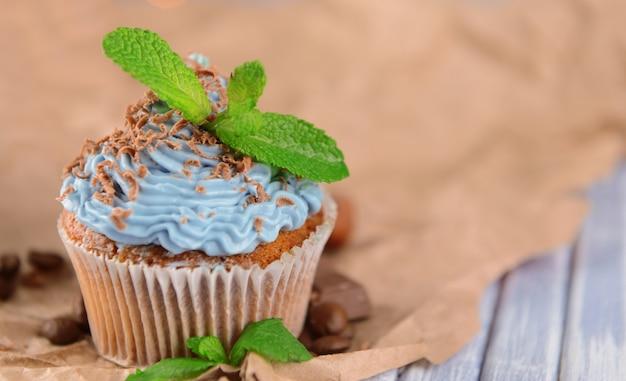 Вкусный кекс со сливочным кремом, на цветном деревянном столе, на поверхности света