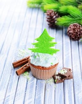 컬러 나무 테이블에 버터 크림을 곁들인 맛있는 컵케이크