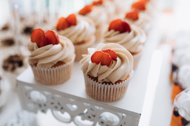 Tasty cupcake with creamy topping and slice of strawberry on the top, sweet buffet