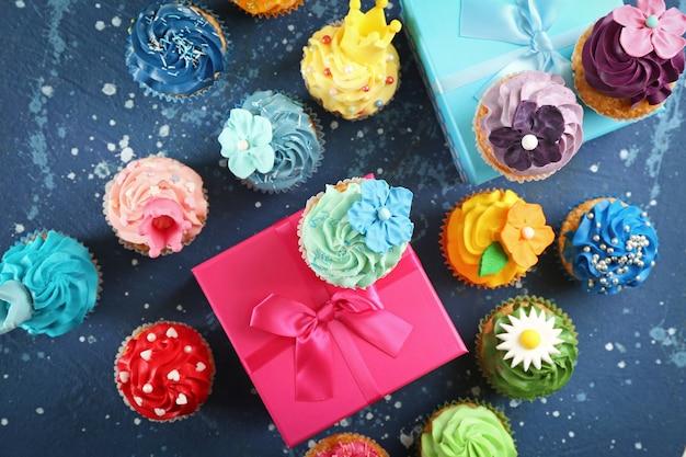 青いテーブルの上のおいしいカップケーキと誕生日プレゼント