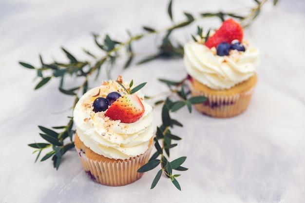 クリームチーズ、ブルーベリー、ストロベリーで飾られたおいしいカップケーキ