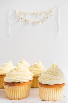 Tasty cupcakes and just married bunting on white background