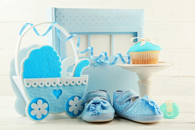 弓とベビーシューズの装飾的なベビーカーと色の背景にフォトアルバムとおいしいカップケーキ