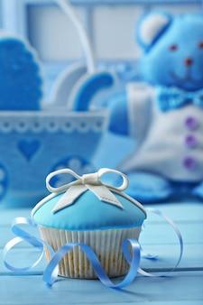 弓とベビーシューズ、装飾的なベビーカーとおいしいカップケーキ