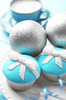 컬러 나무 배경에 활, 커피 컵, 크리스마스 장난감이 있는 맛있는 컵케이크
