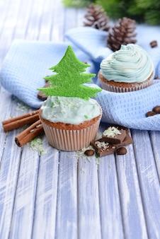 色の木製の背景にバタークリームとおいしいカップケーキ