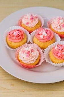 クリームと木製の机の上の白い皿に振りかけるおいしいカップケーキ