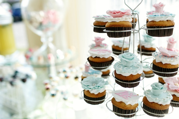 Tasty cupcakes with pink and blue glaze roses put in holders