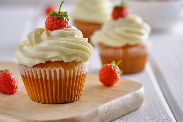 딸기와 흰색 배경 클로즈업에 부드러운 크림과 함께 맛있는 컵 케이크