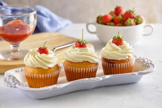 딸기와 흰색 배경에 부드러운 크림과 함께 맛있는 컵 케이크