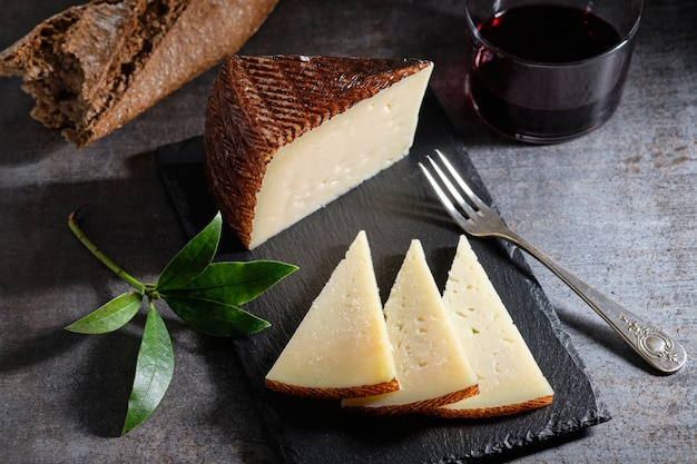 Tasty cured manchego cheese with glass of wine