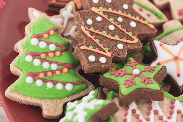 Tasty and cute baked christmas cookies (gingerbread) with beautiful xmas decoration in red plate on light wooden table background, close up, copy space (text space)
