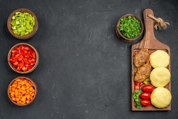 Tasty cutlets vegetables and greens on dark background
