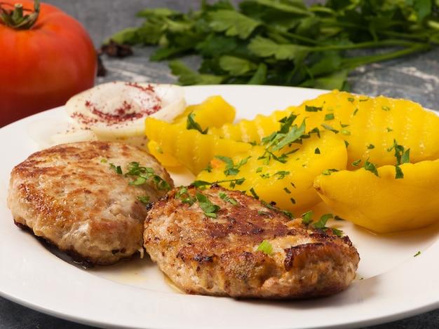 Вкусные котлеты с картофелем на белой тарелке.