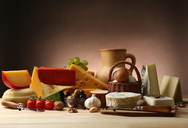 Вкусные молочные продукты на деревянном столе на коричневой стене