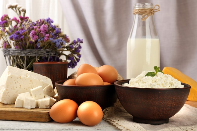 Tasty dairy products with bread and dry flowers on table on fabric