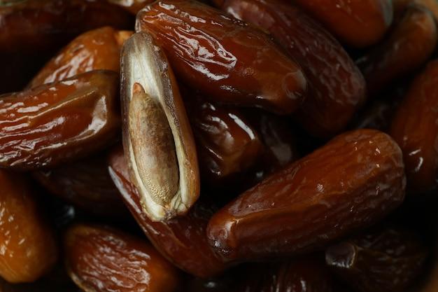 Tasty dates fruits on whole background, close up