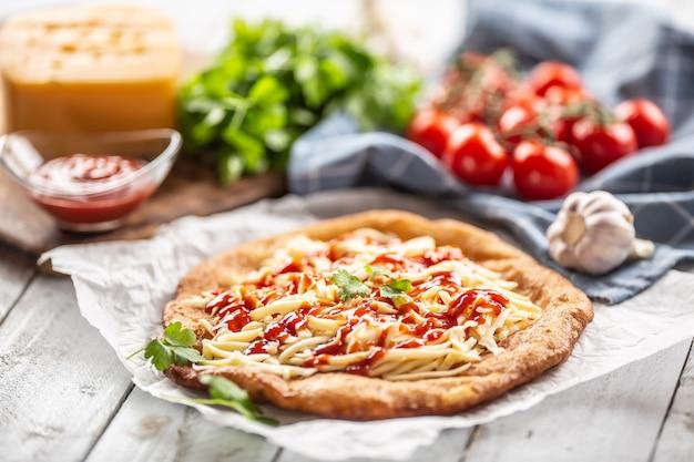 Вкусные жареные ланго на бумаге для выпечки с большим количеством тертого сыра, кетчупа, зеленью и помидорами на проверенной посуде.