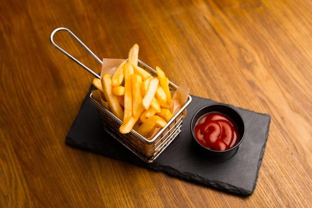 나무 테이블 위에 바구니에 맛있는 맛있고 신선한 튀긴 프랑스 감자