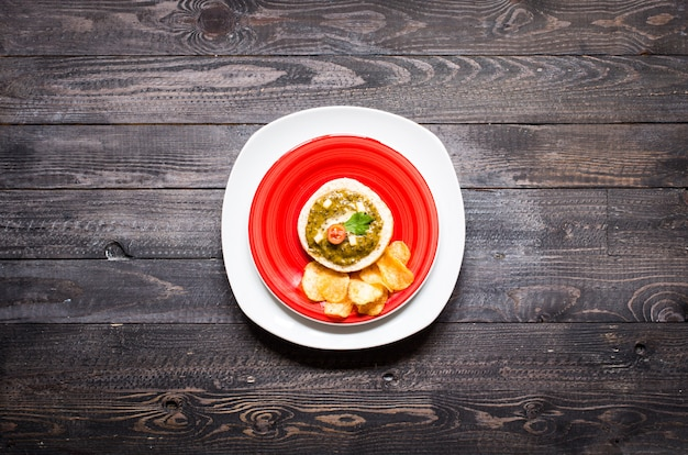 Tasty and delicious bruschetta with avocado, tomatoes, cheese, herbs, chips and liquor, on a wooden background.