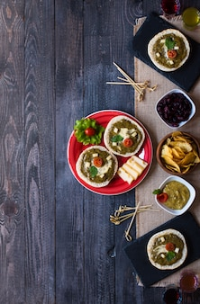Tasty and delicious bruschetta with avocado, tomatoes, cheese, herbs, chips and liquor,.