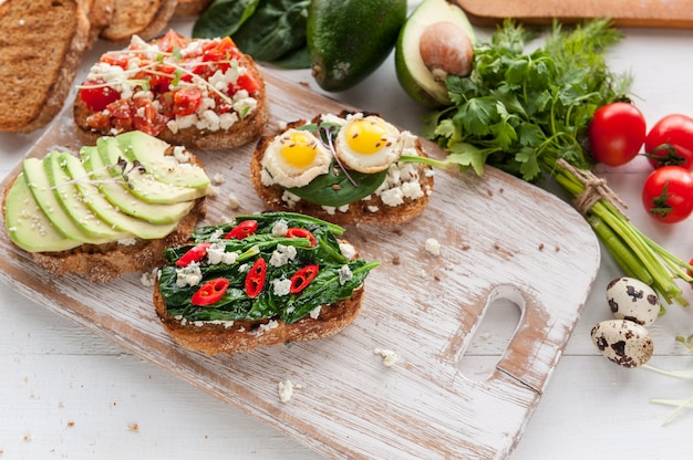 Tasty and delicious bruschetta with tomatoes, spinach, feta avocado red chili pepper and blue cheese.