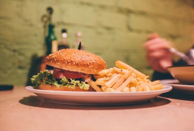 카페에서 접시에 맛있는 맛있는 햄버거. 육즙이 많은 햄버거와 함께 감자 튀김.