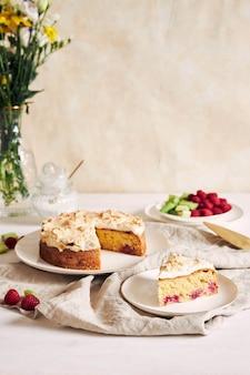 Torta gustosa e deliziosa con baiser e lamponi su un piatto