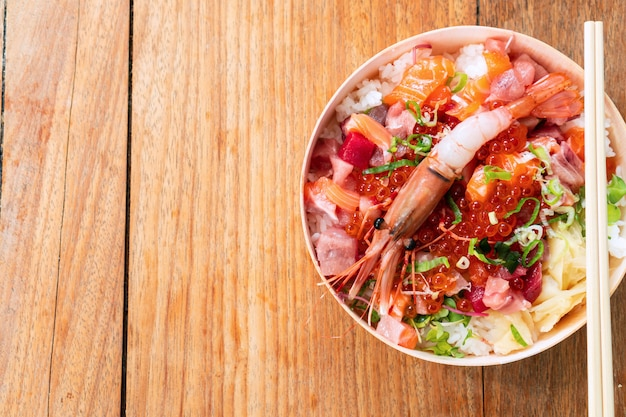 Tasty and delicious chirashi japanese food on wooden table, healthy eating and eat well concept. take away home food. top view, copy space