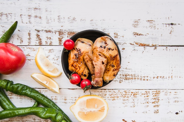 Tasty delicious roasted chicken in bowl with lemon; tomato; green chilies on wooden desk