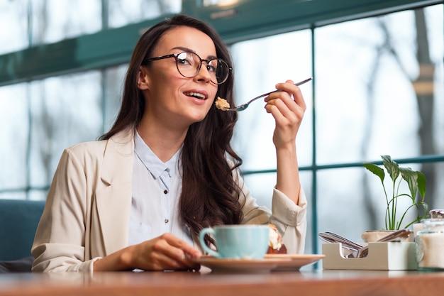 Вкусная пустыня. низкий угол мечтательной приятной женщины, смотрящей в камеру во время дегустации еды и кофе