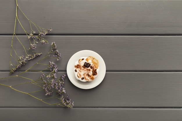 Tasty dessert background. chocolate cake on gray rustic table with violet flowers, provence style, top view, copy space