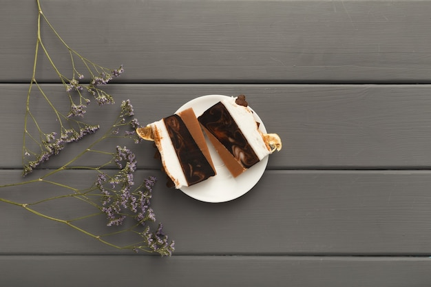 Tasty dessert background. chocolate cake pieces on gray rustic table with violet flowers, provence style, top view, copy space