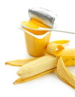白で隔離のオープンプラスチックカップとバナナのおいしいデザート