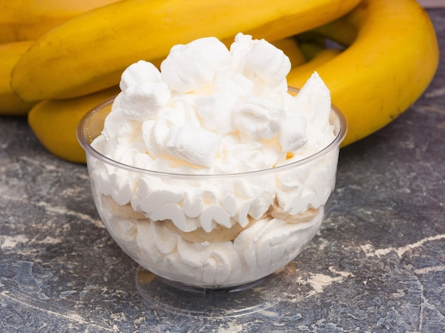 おいしいデザート:灰色の背景のクリームボウルにバナナとホイップクリーム